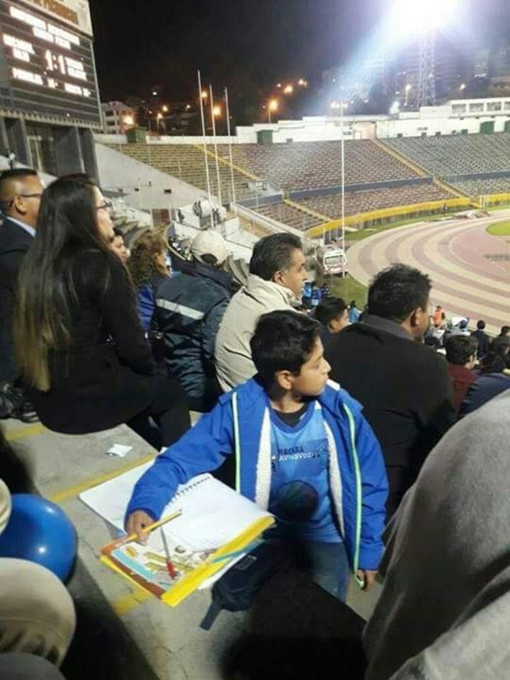 Niño hace la tarea en el estadio para no perderse el partido de futbol (FOTOS)